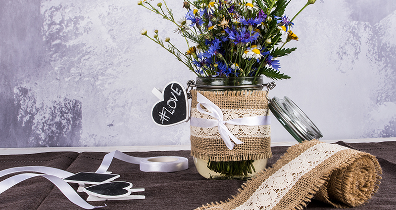 Meadow flowers in a jar decorated with jute and a clasp lid next to a linen strip, a ribbon and other decorations