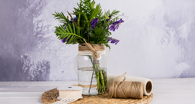 Meadow flowers in a jar decorated with lace and jute next to a linen string and a  a spool of netting