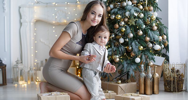 Mom with her son in front of a Christmas tree in a light room, gifts next to them.