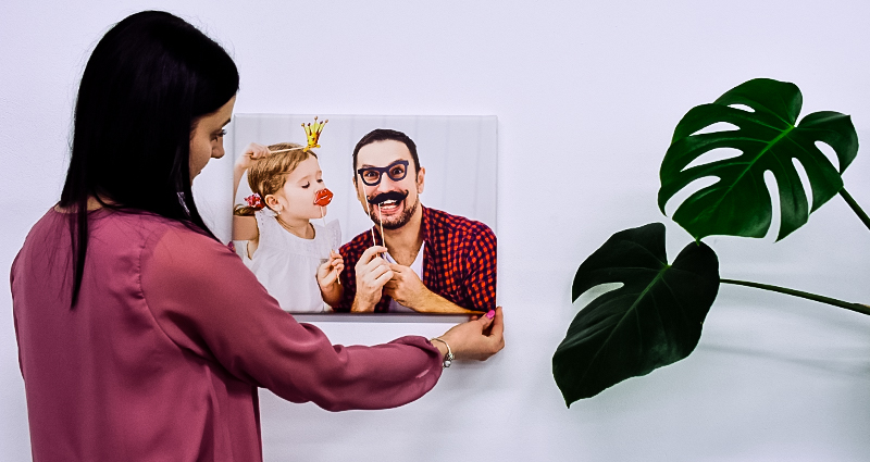 Woman hanging a father and daughter picture