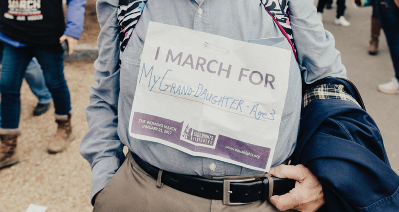 "Old man holding a piece of paper with note on it: ""I march for my granddaughter, age 9""."