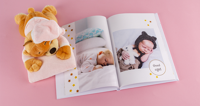 Photo book of a newborn baby's picture next to a teddy bear