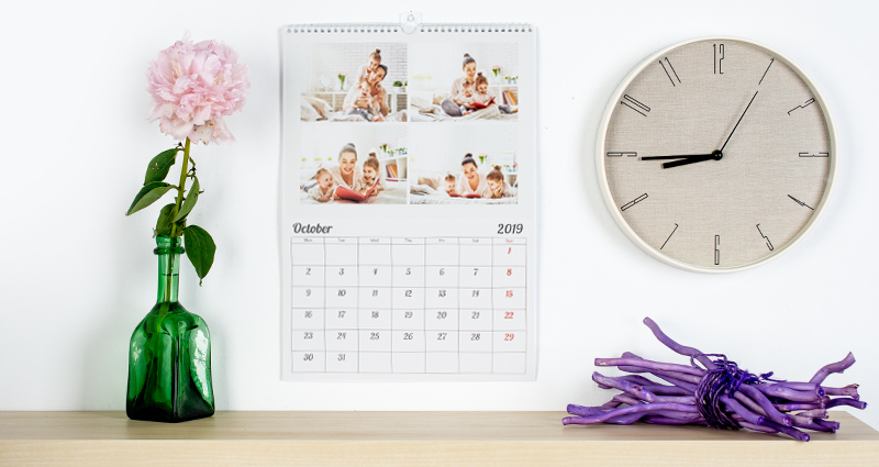 Photo calendar with 4 photos hanging on a wall next to a round clock; there is a shelf with a flower vase below it.