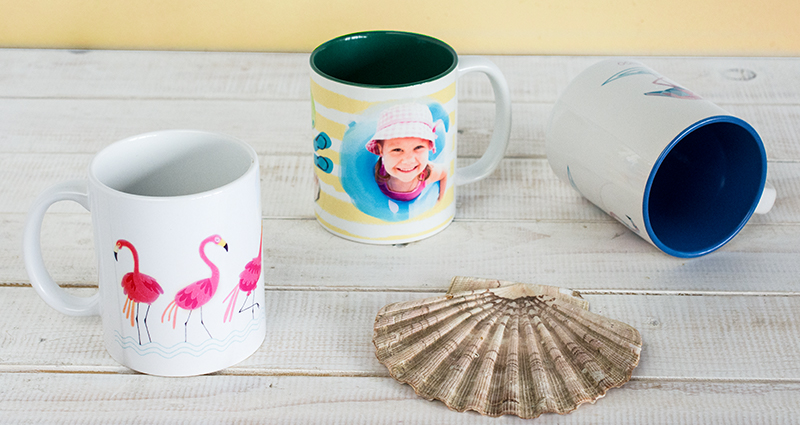 Photo mugs on the desk – one mug with a photo, two mugs with a pre-made template lying next to a seashell.