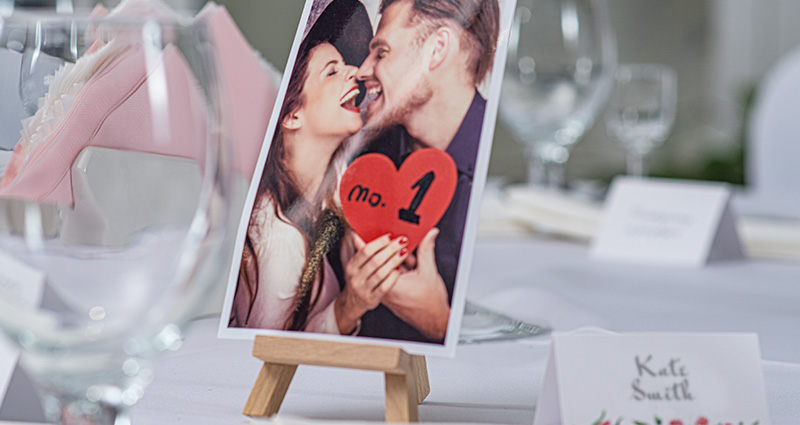 "Photo of a couple in love, holding a read heart which reads ""No.1"", on a miniature wooden easel indicating the table number. Tableware and wedding guest's name card near."