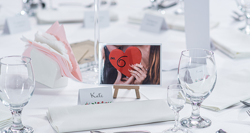 "Photo of a couple in love, holding a red heart which read ""No. 6"", on a miniature wooden easel indicating the table number. Tableware and wedding guest's name card near."