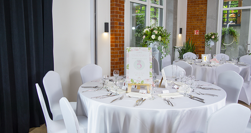 Photo of a decorated in white round wedding table in a ballroom. Tableware, bouquet of flowers, a pastel photo canvas with a table number and a thank you note for the guests on the table.