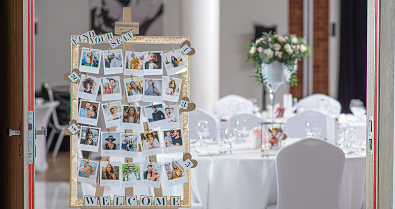 "Photo of a handmade frame with photos of the wedding guests situated near specific table numbers. ""Find your seat"" caption at the top and a ""Welcome"" caption at the bottom of the frame. One of the ballroom tables in the background."