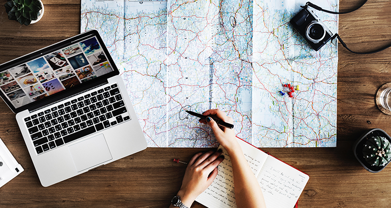 Photo of a person getting ready to his/her journey: world map in the center, laptop, camera and notebook on a desk