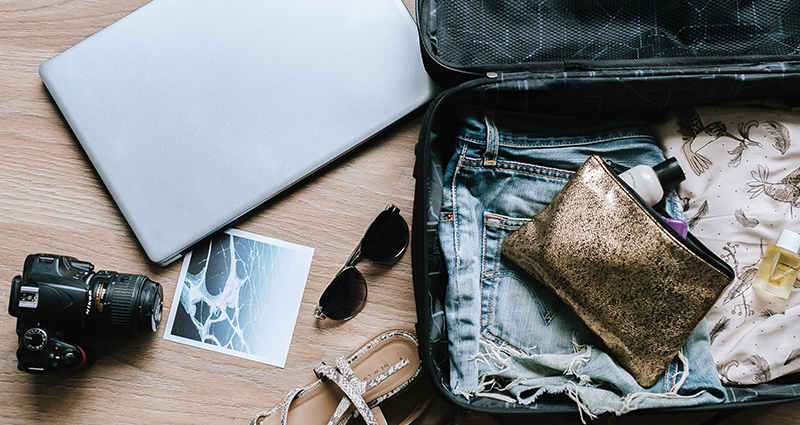 Photo of an open suitcase, things on the floor that are ready to be packed