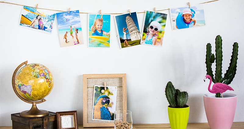 Photo of holiday prints hanging on a string and pinned with wooden clips; a globe put on a retro box on the left, two cactuses in coloured flowerpots on the right.