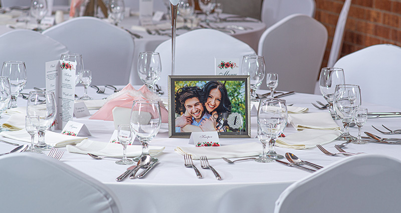 Photo of the newly-weds, taken during the wedding photo session, in a black-silver frame and with a number 1 set in the middle of the wedding table decorated in white. Tableware and name cards all around.