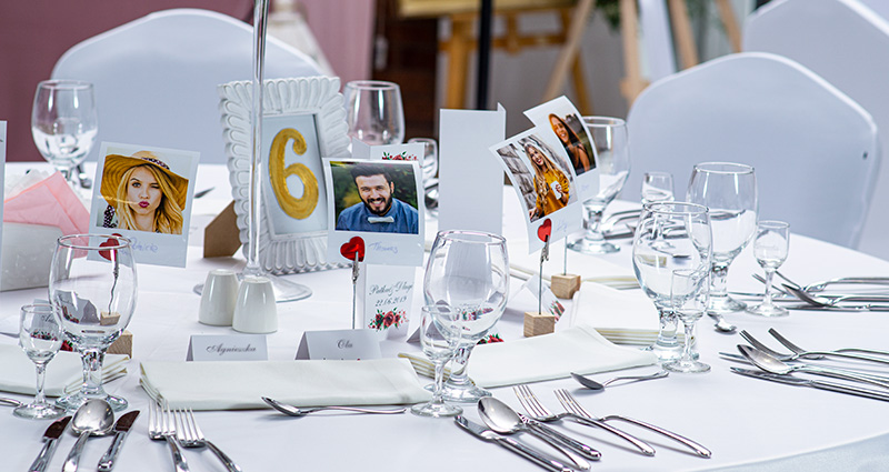 Photo place cards with pictures of your guests printed with the use of our Retro Prints format, all captioned with their names. The decorations are placed on a table covered with a white cloth, next to the crockery