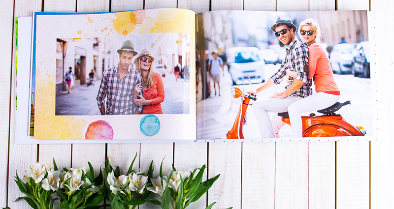 Photos of a couple in a pastel-coloured album on a white wooden background, flower decorations below.