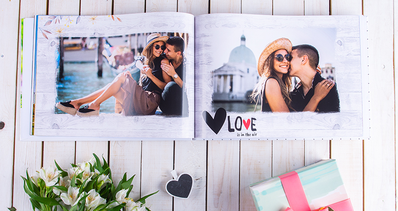 Photos of a couple in an album. 'Love is in the air' caption below a photo. Photo book on a white wooden background, flower decorations and colourful gift below that.