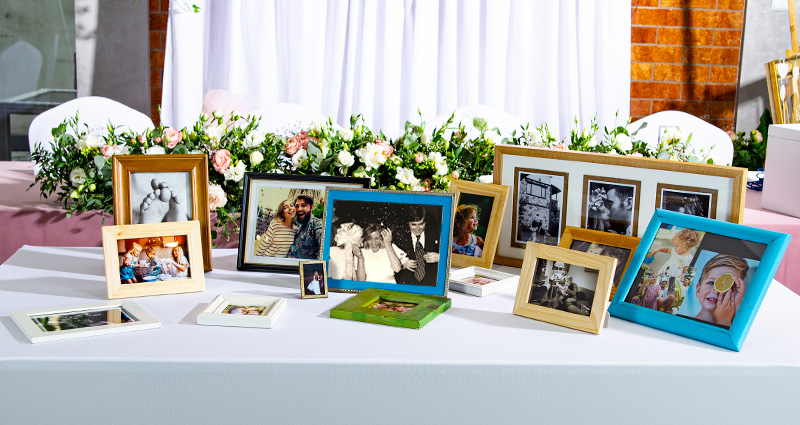 Photos of the newly-weds and their parents from different stages of life in colourful frames placed on a white table (the photo-corner of memories). A table decorated with flowers in the background, white lanterns on both sides of the table