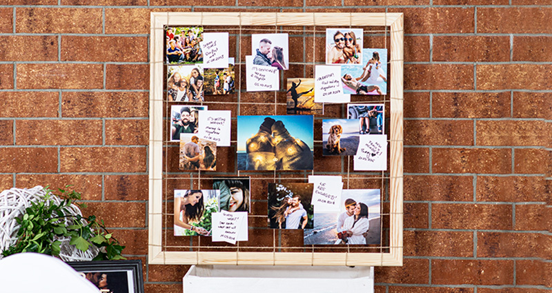 Photos of the newly-weds, showing their love story, attached to a hemp string tied to a wooden frame, captions placed next to the photos. The frame stands on a white box, a red brick wall in the background