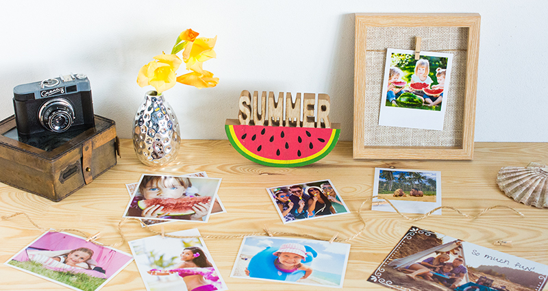 Rectangular prints, insta photos and retro print on the desk; a wooden photo frame, flowers in a flower vase, a camera and other accessories in the background