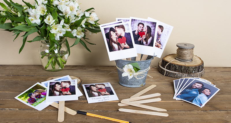 Retro prints on an ice cream sticks in a decorative pot, arranged photos, sticks and black marker placed next to it, white flower bouquet in a vase and spool of jute string on a wooden disc in the background.