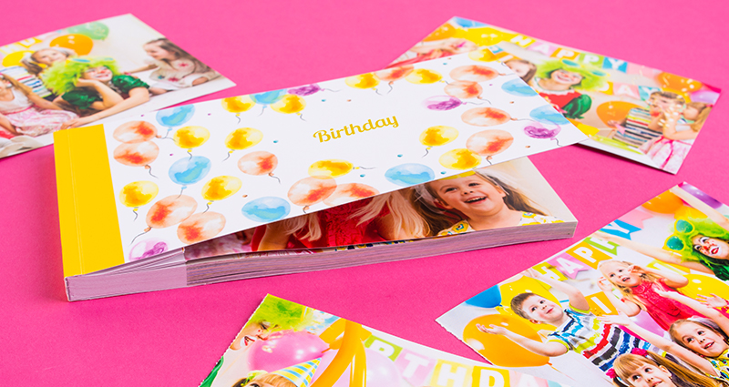 Sharebook with the Colourful Balloons cover, torn-away pictures of a children's birthday party lying around it.