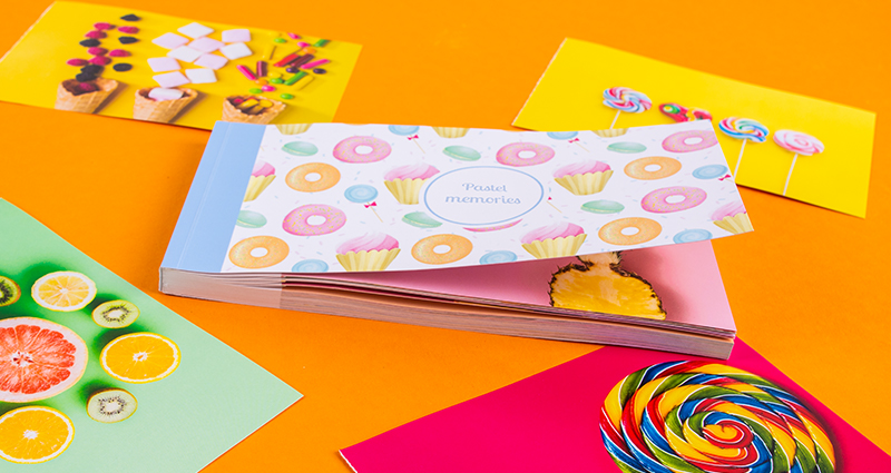 Sharebook with the Pastel Sweets cover, torn-away pictures showing sweets in strong colours lying around it