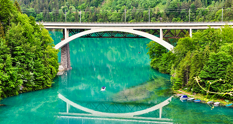 Tall bridge in the forest reflected in a turquoise water surface
