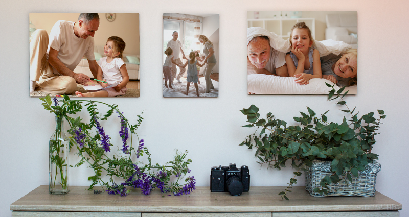 Three family photo canvases hanging on a cream wall; two flower vases and a camera on a grey cupboard.