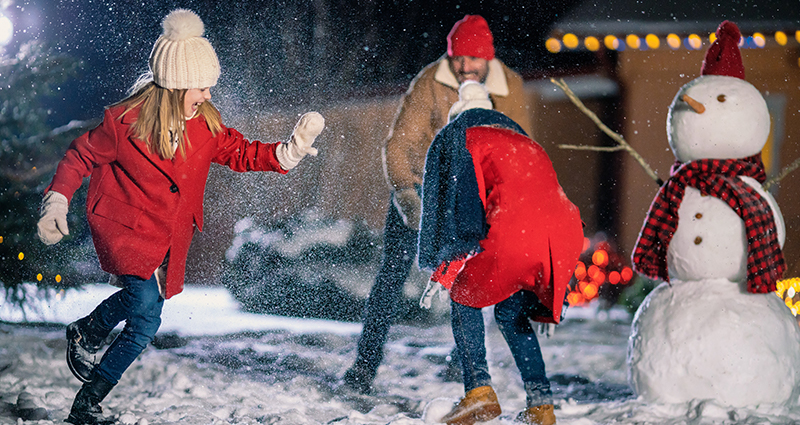 Two girls throwing snowballs on a winter evening