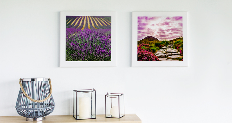 Two landscape photo canvases on the wall above a bookshelf with 3 candlesticks
