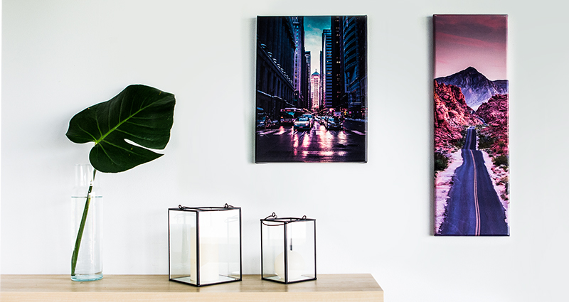 Two new formats of photo canvases hanging on the wall over a bookshelf with candlesticks and a monstera leaf in a flower vase