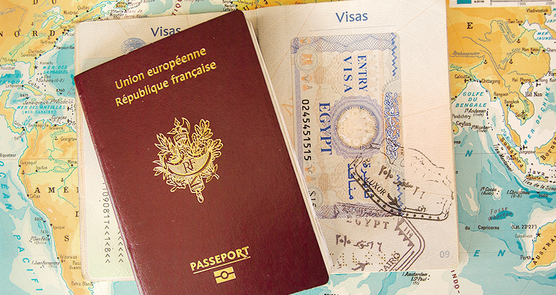 Two passports, one opened, world map in the background