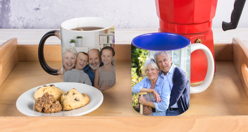 Two personalised photo mugs on a wooden tray, cookies on a plate and a red moka pot next to it.