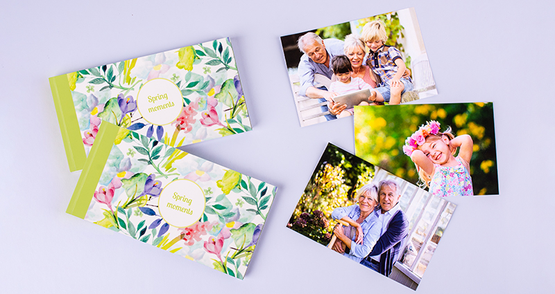 Two sharebooks with the Spring Flowers cover lying next to three family photos