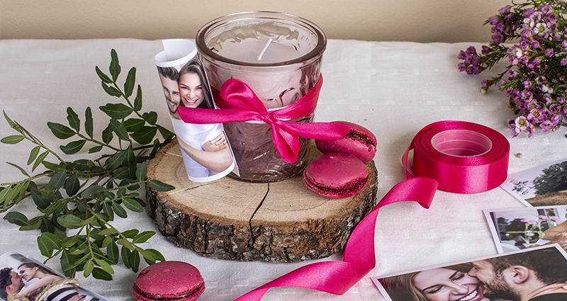A pink candle in a jar with a rolled-up picture of a couple tied with pink ribbon on a wooden disc. Pink macarons, prints, spool of ribbon, green decorative brunch and tiny pink flowers placed around. A composition on a white tablecloth.