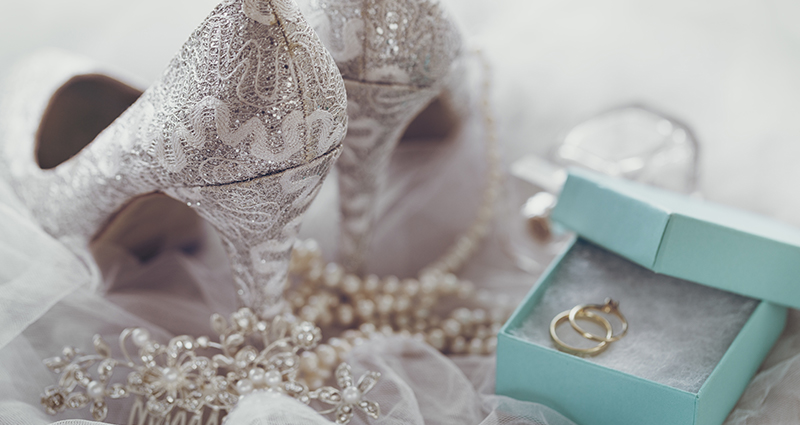 Wedding accessories: shoes, hair decoration, a square decorative box with a wedding ring and an engagement ring inside