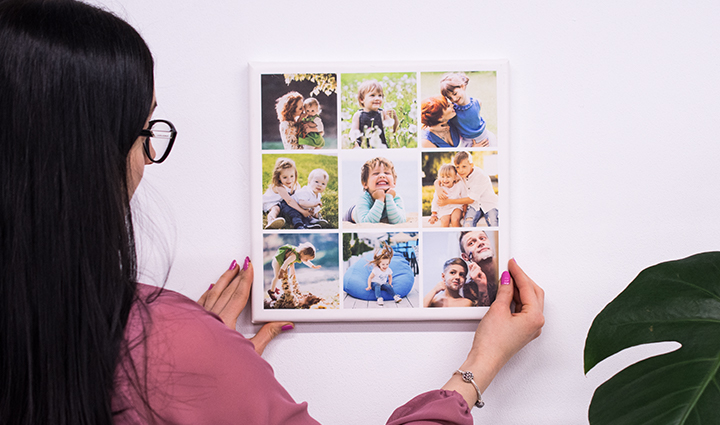 Woman hanging a square photo canvas in the form of collage