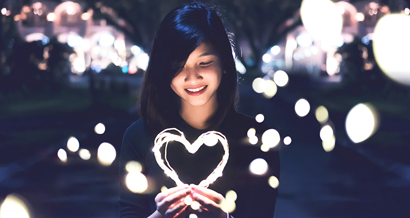 Woman holding a lighted heart