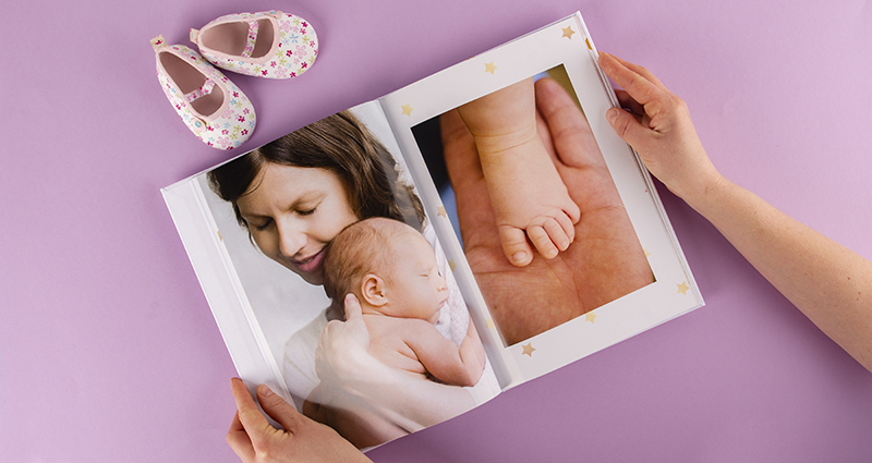 Woman holding a photo book from a newborn baby's photo shoot, booties on the top