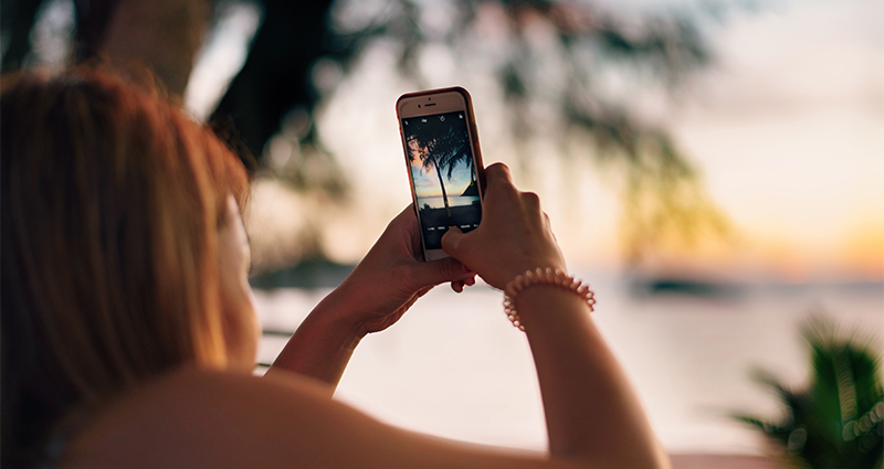 Woman taking picture of a palm tree at sunset
