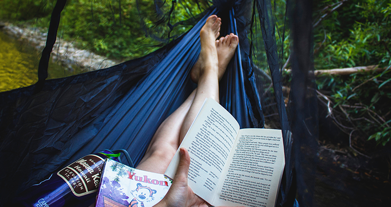 Woman's legs who is reading a book in a hammock in the jungle.