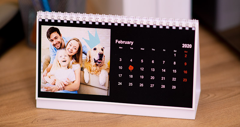 A personalised desk calendar with a black background and clipart