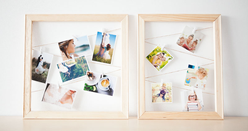 Photos on strings in wooden frames.