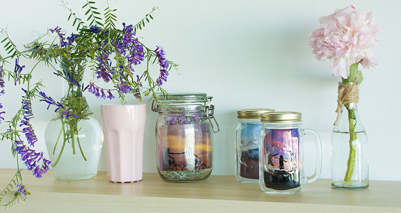 An arrangement of holiday photos in jars on a shelf.