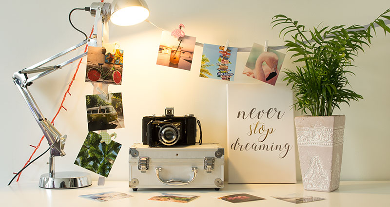 An arrangement with insta photos and a photo canvas on a desk.