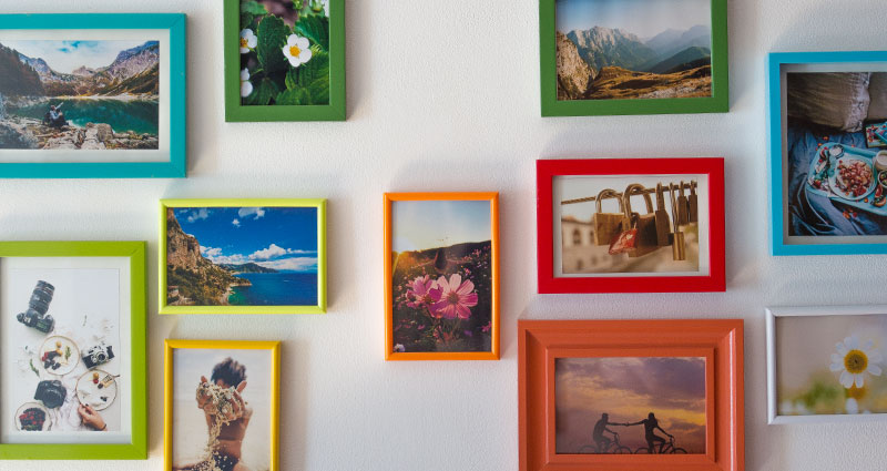 Close-up on photos in coloured frames hung on a wall.