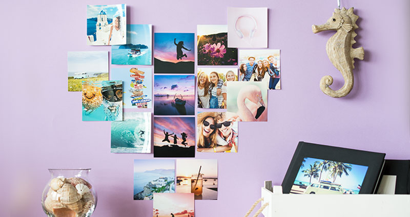 Insta photos in heart-shape on a purple wall.