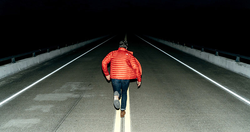 A flash photo of a running man at night.