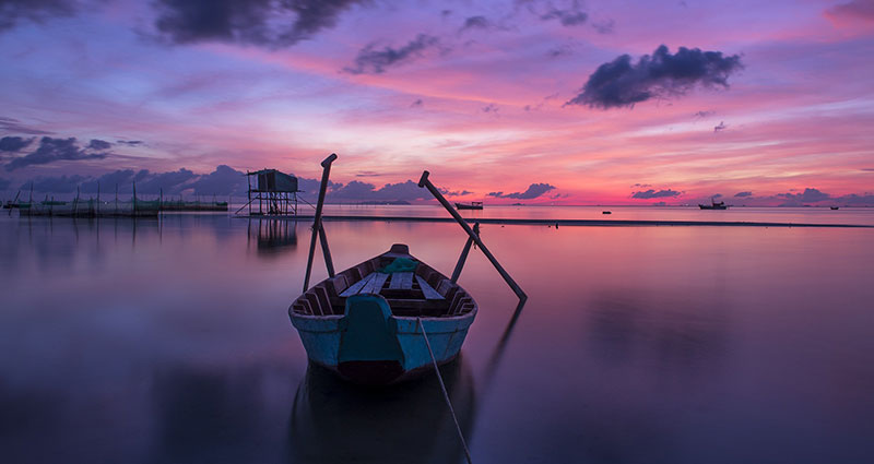 A boat on the lake in violet colours.