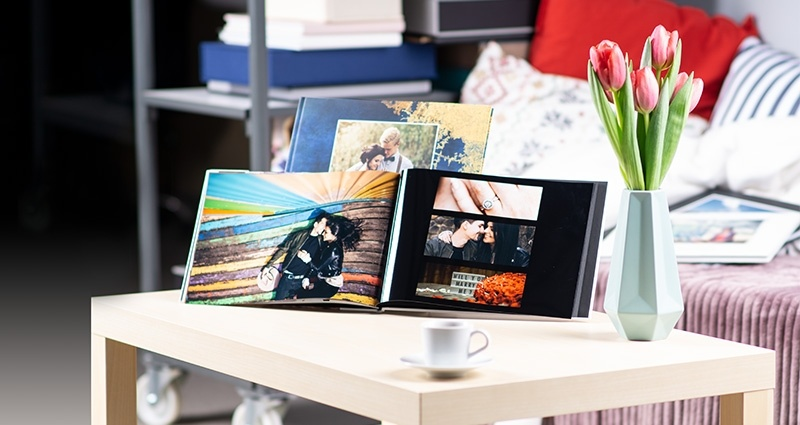 2 starbooks, with pictures of a couple, on a bright table and tulips in a vase next to them. A couch in the background and photo products on the shelves.