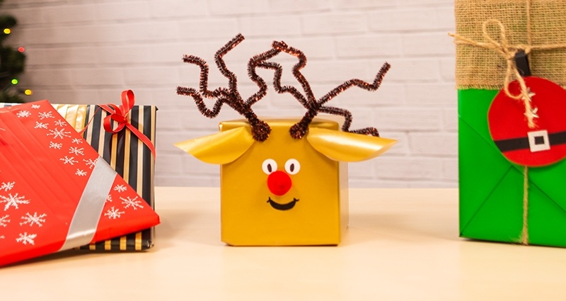 "2 wrapped books, a reindeer gift box and a gift wrapped in the Kimono style lying on the desk. A brick wall, hanging letters ""Merry Christmas"" and a Christmas tree in the background."